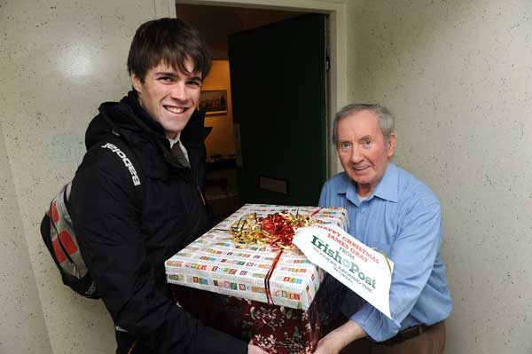 Niall O'Sullivan presents James with one of four boxes of cards and gifts from Irish Post readers