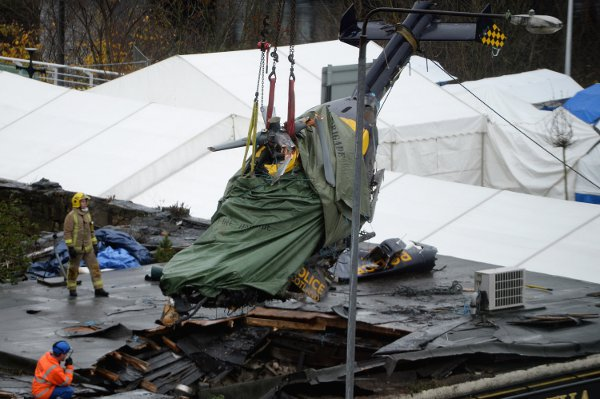 Rescuers lift the police helicopter wreckage from the roof of the The Clutha Pub   (Photo by Jeff J Mitchell/Getty Images)