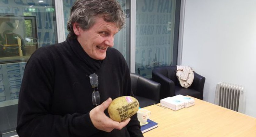 Dermot Bradley with the potato his sister posted from England. Picture via BBC NI