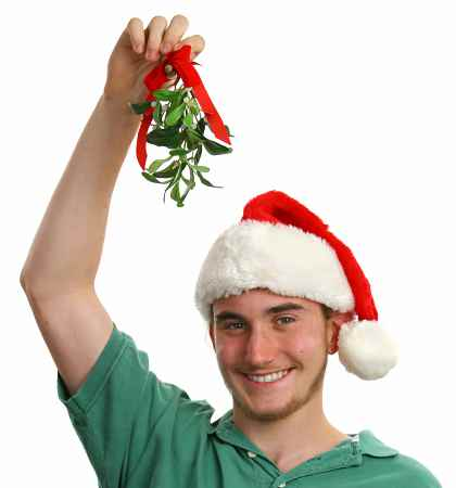 A teen boy wearing a santa hat and holding mistletoe over his head. Isolated.
