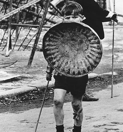A young boy with a bin lid as a shield plays warrior on the streets of Ulster. (Photo by Three Lions/Getty Images)