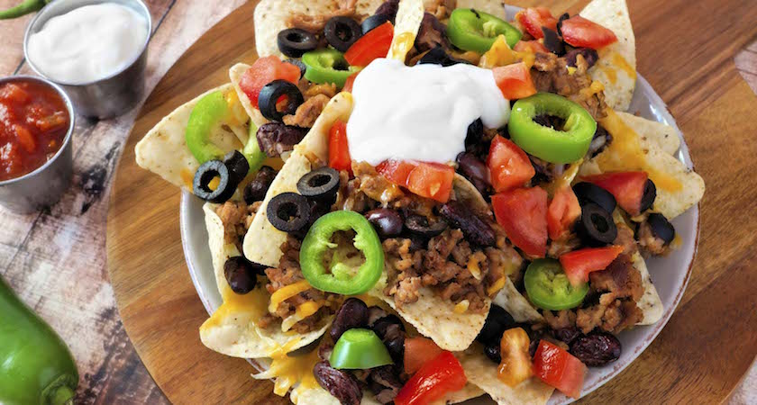 Mexican nacho chips topped with sour cream, ground meat, jalapenos, tomatoes, beans and melted cheese on a wooden paddle board
