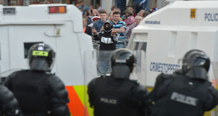 A Loyalist breaks through a police barrier and taunts police officers as Orangemen are prevented from progressing on the return journey towards the controversial Ardoyne flashpoint the Twelfth of July parade on July 13, 2015 in Belfast. (Getty)