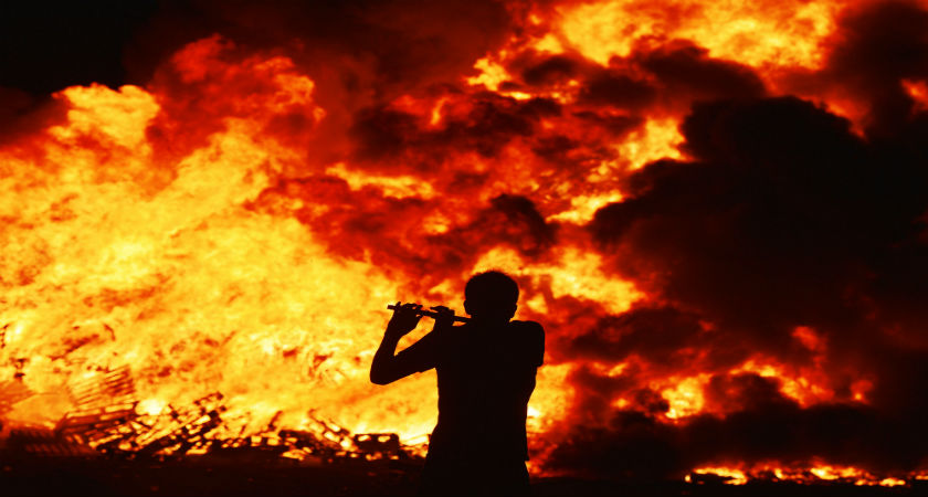 Iain McFarland, an Orange bandsman, plays his flute during the 11th night bonfire at the New Mossley housing estate on July 12, 2015 in Belfast. (Getty)