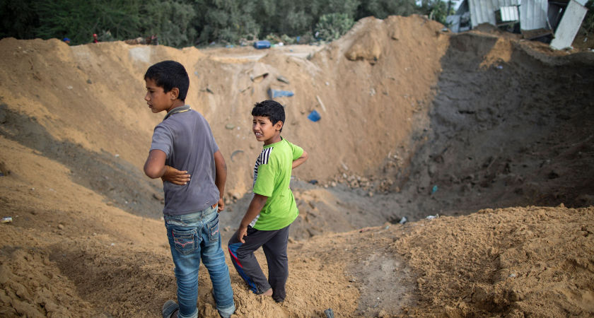 Palestinian children stand next to a crater on August 22, 2016 in Beit Lahia in the northern Gaza Strip, following an Israeli airstrike [Picture: Getty]