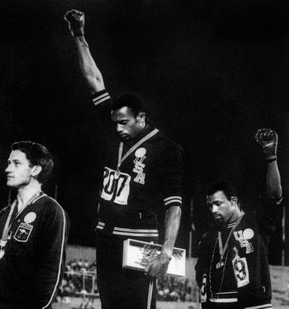 Tommie Smith (C) and John Carlos (R) raise their gloved fists in the Black Power salute to express their opposition to racism in the USA [Picture: Getty]