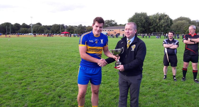 Lancashire GAA Chairman Sean Breathnach presents the trophy to John Mitchells captain Pauric McGuirk