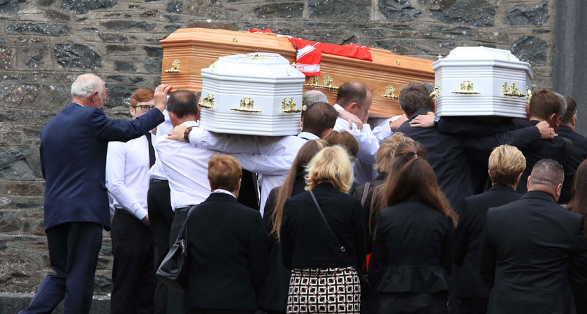 The coffin of Alan Hawe on the left with his GAA club colours on top and the coffins of two of his sons arrive at the church for the funeral Mass (Photo: RollingNews.ie)