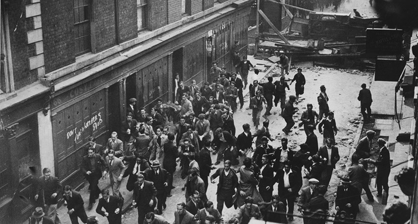 Demonstrators flee down Cable Street as Police target the barricade [Source: Getty/Topical Press Agency]