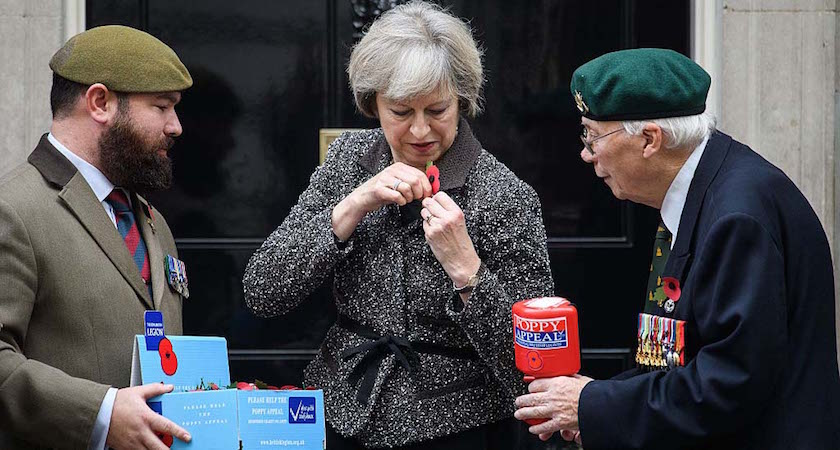 """LONDON, ENGLAND - OCTOBER 31: British Prime Minister Theresa May (C) attaches her poppy as they take part in a photocall for this years """"Poppy Appeal"""" with veterans Stewart Harris (L) and Roy Miller (R) at Downing Street on October 31, 2016 in London, England. This year, The Royal British Legion is asking the nation to """"Rethink Remembrance"""" by recognising the sacrifices made not just by the Armed Forces of the past, but by today's generation too. (Photo by Leon Neal/Getty Images)"""