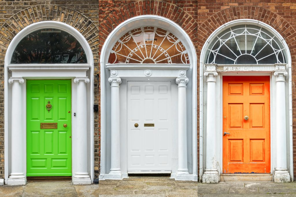 A set of doors lined up to match the colours of the Irish flag.