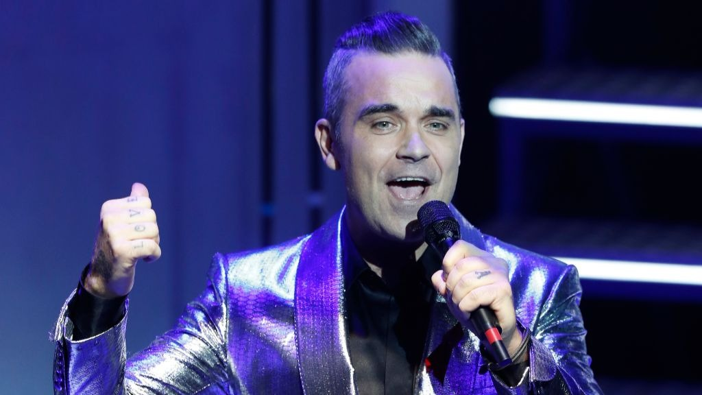 Robbie Williams claims his signature hit 'Angels' was inspired by an encounter with a ghost.