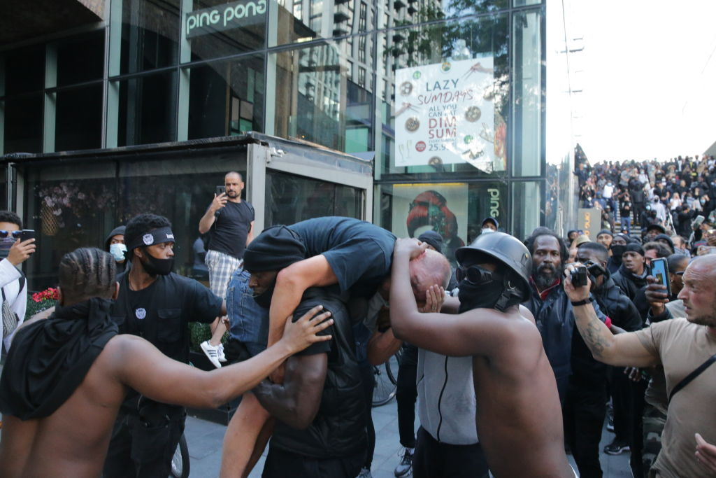 Black Demonstrator Carries Injured Far-Right Protester Out Of Hostile Crowd