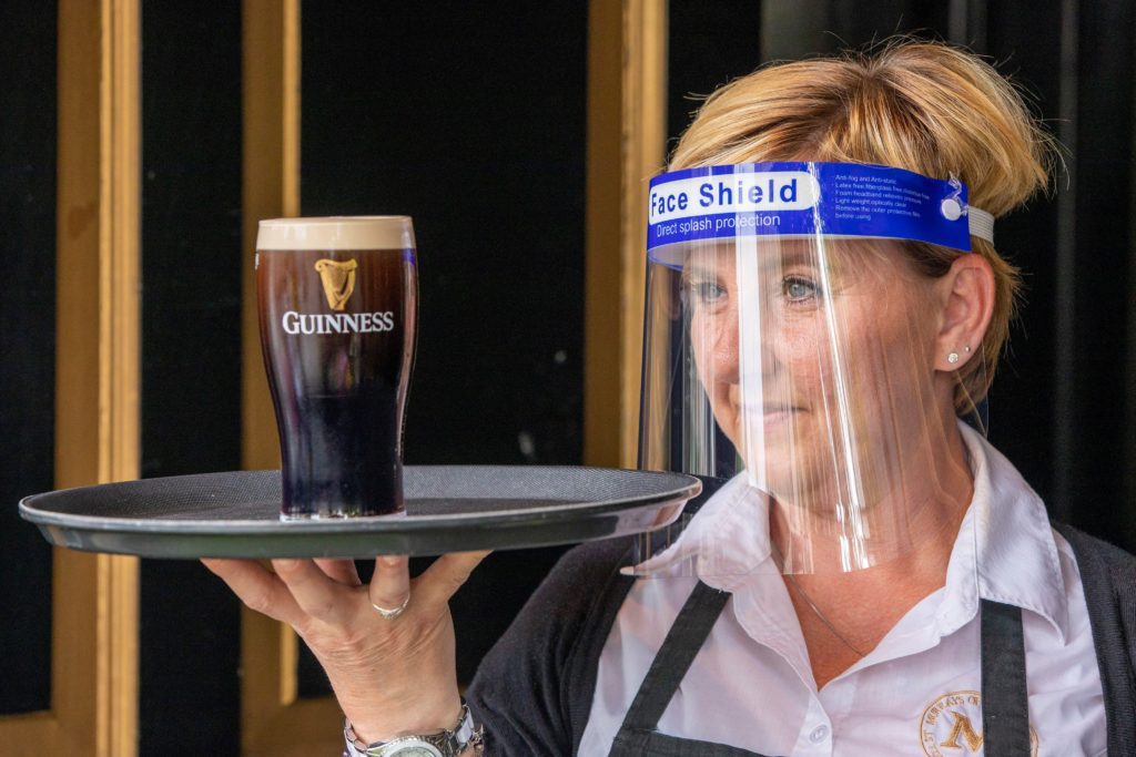 PPE on staff member holding pint of Guinness in Irish pub