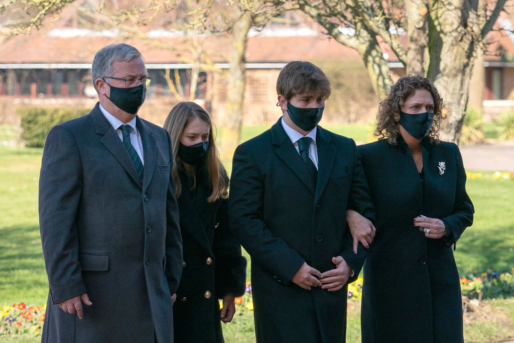 BEDFORD, ENGLAND - FEBRUARY 27: (No reuse after 11.59pm on March 6th 2021 without written consent from gemma@captaintom.org.) The family of Captain Sir Tom Moore (left to right) son-in-law Colin Ingram, granddaughter Georgia, grandson Benjie and daughter Hannah Ingram-Moore arrive for his funeral at Bedford Crematorium on February 27, 2021 in Bedford, England. WWII veteran, Sir Tom raised nearly £33 million for NHS charities ahead of his 100th birthday last year by walking laps of his garden in Marston Moretaine, Bedfordshire. He died on the 2nd of February after testing positive for COVID-19.